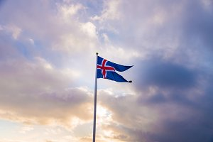 Waving Icelandic flag against cloudy sky.