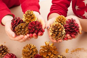 Children holding painted pine cones