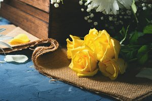Yellow roses on rustic background