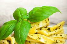 Cooked homemade pasta with pesto and basil