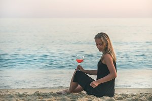 Woman sitting with wine on beach