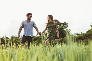 Young couple walking in field