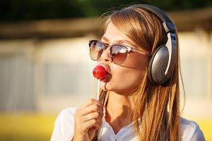 Girl licks lollipop.