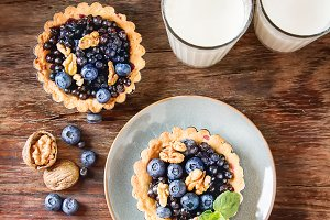 Homemade blueberry tart, walnut and mint with milk on a dark wooden table, French culture