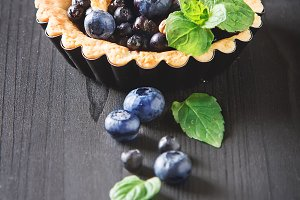 Homemade blueberry tart, walnut and mint on dark wooden table. French culture