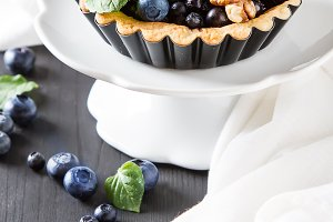 Homemade blueberry tart, walnut and mint on dark wooden table white cloth. French culture