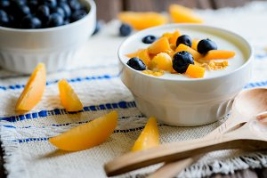 Yogurt with fresh blueberries, corn flakes and apricots on a textural brown surface