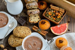 Two cups of fresh hot cocoa or hot chocolate with muffins, juice and raisin cake on wooden background, top view
