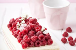 Cake with cream and fresh raspberries