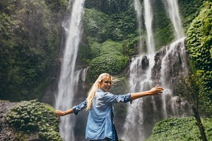 Tourist enjoying by a waterfall