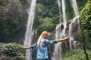 Tourist enjoying by a waterfall