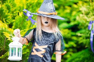 Adorable amasing little girl wearing witch costume on Halloween outdoors. Trick or treat.