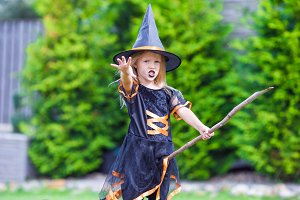 Adorable little girl wearing witch costume on Halloween outdoors. Trick or treat.