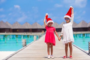 Little adorable girls in red Santa hats on beach tropical vacation