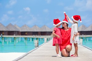 Happy family in Santa hats during Christmas tropical vacation