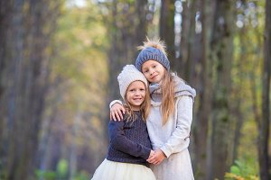 Little adorable sisters at warm sunny autumn day outdoors
