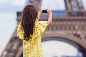 Young woman making photo by phone background Eiffel Tower in Paris