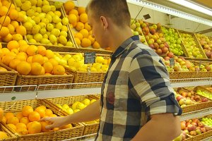 Man selecting fresh fruits in grocery store produce department and putting it in plastic bag. Young guy is choosing oranges in supermarket and putting them into shop basket