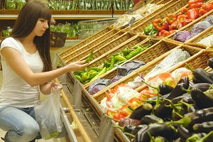 Young pretty girl is choosing peppers in a grocery supermarket. Attractive woman selecting fresh green peppers in grocery store produce department.