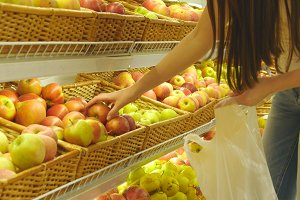 Woman selecting fresh red apples in grocery store produce department and putting it in plastic bag. Young pretty girl is choosing apples in supermarket and putting them into shop basket