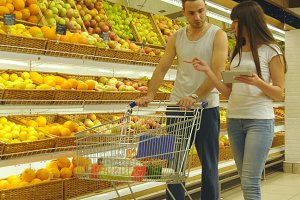 Young caucasian couple walking in a supermarket with a market trolley and choosing fresh apples. Man is putting fruits into the shop basket. Woman is using tablet pc to check shopping list