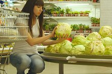 Young couple with supermarket trolley are walking in the grocery department at the shopping mall. Woman is sitting down, choosing cabbage and putting it into the basket