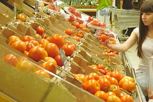Young pretty girl is choosing tomatoes in a grocery supermarket and talking. Attractive woman selecting fresh ripe red tomatoes in grocery store produce department.