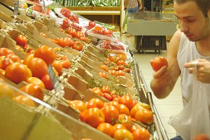 Young man is choosing tomatoes in a grocery supermarket and smiling. Happy guy selecting fresh ripe red tomatoes in grocery store produce department.