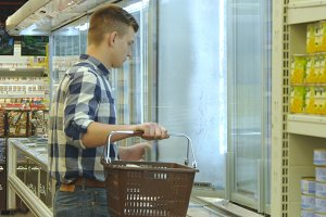 Young man with shopping cart buying dairy or refrigerated groceries at the supermarket in the refrigerated section opening glass door. Guy coming up to the fridge in shop and taking product from it