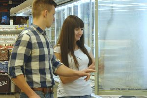 Young happy couple is standing by the freezer in grocery store and picking packages with frozen food. Girl taking product from the fridge and smiling