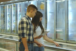 Young couple is standing by the freezer in grocery store and picking packages with frozen food. Man taking product from the fridge. Woman using tablet pc to check shopping list