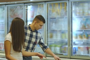 Young happy couple is standing by the freezer in grocery store and picking packages with frozen food. Man taking product from the fridge