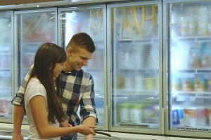 Young happy couple is standing by the freezer in grocery store and picking packages with frozen food. Man taking product from the fridge and smiling