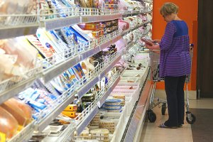 Old woman with shopping cart buying dairy or refrigerated groceries at the supermarket in the refrigerated section. Grandmother stay near the fridge in shop and taking product from it