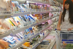 Young woman with shopping cart buying dairy or refrigerated groceries at the supermarket in the refrigerated section. Girl coming up to the fridge in shop and taking product from it