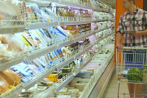 Young man with shopping cart buying refrigerated groceries at the supermarket and using tablet pc to check shopping list. Guy coming up to the fridge in shop and taking product from it