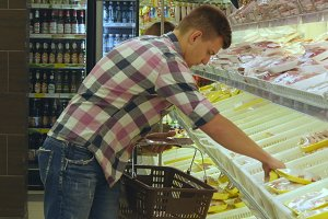 Man with shopping cart buying refrigerated groceries at the supermarket and using tablet pc to check shopping list. Guy coming up to the fridge in shop, taking product and putting it into the basket