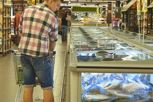 Young man with shopping cart buying refrigerated groceries at the supermarket in the refrigerated section opening glass door. Guy coming up to the fridge in shop and taking product from it. Rear view