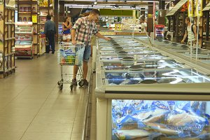 Young man with shopping cart buying refrigerated groceries at the supermarket. Guy coming up to the fridge in shop and taking product from it