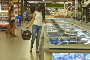 Young woman with shopping cart buying refrigerated groceries at the supermarket. Girl coming up to the fridge in shop and taking product from it