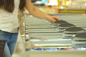 Female hands opening glass door in the refrigerated section at the supermarket and choosing refrigerated groceries. Young woman taking product from fridge in shop and putting it into the basket
