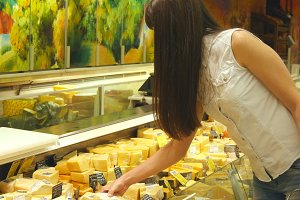 Young woman with shopping cart coming up to the fridge in shop and taking product from it. Girl select cheese in the refrigerated section at store and putting it into the basket
