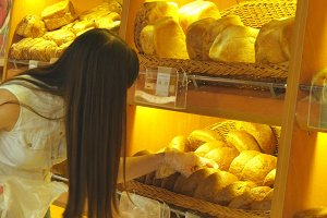 Woman chooses and putting a fresh bread loaf into a package in the supermarket. Young girl taking a loaf of bread from the shelf, smelling it and putting it into the basket. Shopping in the grocery