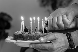 Light candles on birthday cake b/w