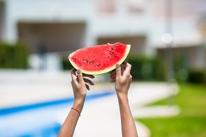Closeup girl female hands with watermelon background swimming pool