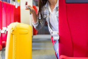 Young happy girl traveling by train with big yellow luggage