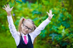 Portrait of adorable little school girl in glasses outdoor