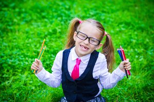 Portrait of adorable little school girl in glasses with pencils outdoor
