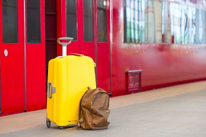 Yellow luggage with passports and brown backpack at train station