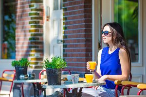 Beautiful woman sitting in outdoors cafe at european city having breakfast
